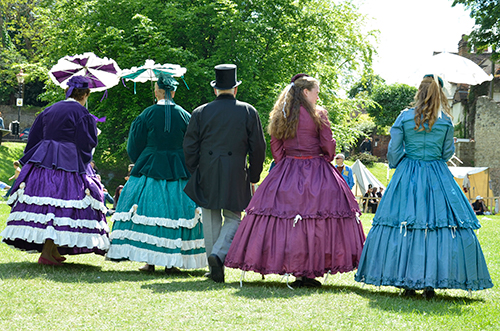 Four actors walking in period dress.